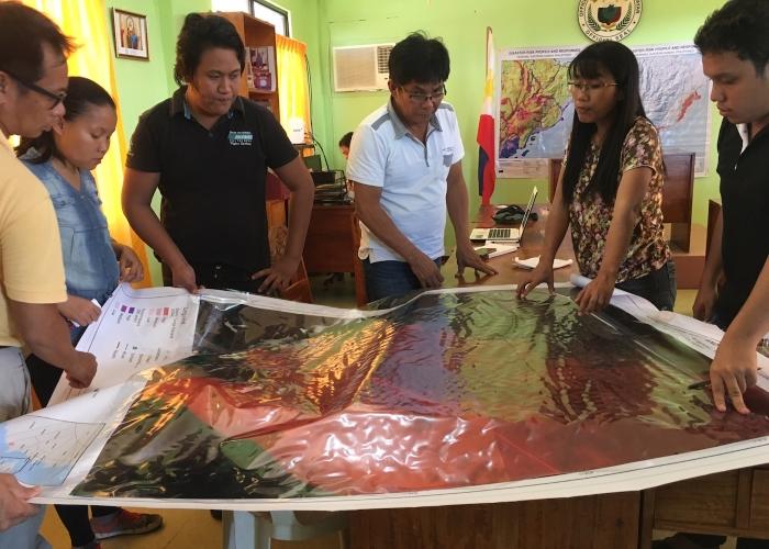 Funcionários do poder local em Samar Oriental e da organização Environmental Science for Social Change observam mapa com indicação de zonas de risco de catástrofe e localização das habitações